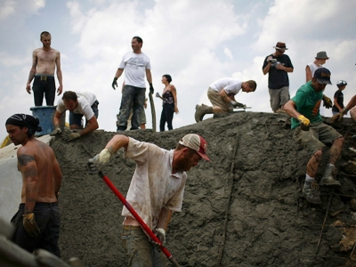 Skatopians pour concrete to expand the park before the Bowl Bash event – credit: Richie Wireman